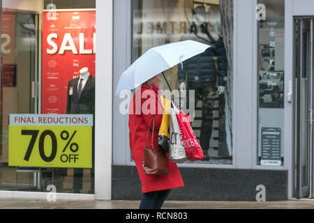 Preston, Lancashire, 16th Jan 2019.  UK Weather. Wet & windy start to the day in the city centre. Rain is moving east across England with heavy showers in the north and west, turning increasingly wintry. Woman passing Sale window carrying Next Sale shopping bags. Discounts, sale, clearance, fashions, clothing store  sales.Credit: MediaWorldImages/Alamy Live News - Stock Photo