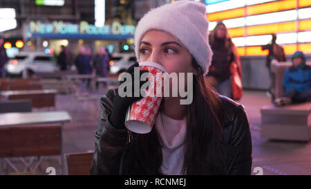 Young woman drinks a cup of coffee in the streets of New York - Stock Photo