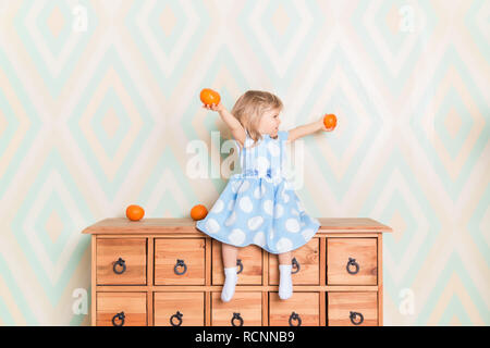 Little girl holding tangerines or oranges in her hands while sitting on the wooden wardrobe. Wearing light blue dress. Christmas holidays is over. Happy smiling baby raising hands up looking aside - Stock Photo