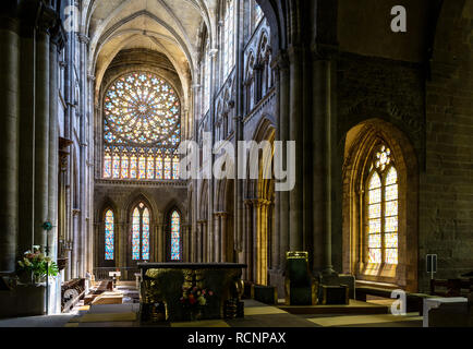 Interior of Saint-Vincent cathedral in Saint-Malo, France, with the large rose window and the sunlight illuminating through the stained-glass windows. - Stock Photo