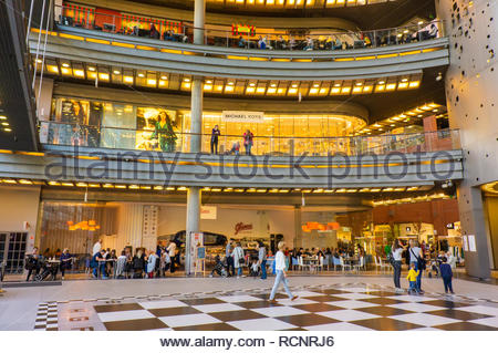 Poznan, Poland - October 13, 2018: Interior of the Stary Browar shopping mall with stores, shops and restaurants. People sitting at ice cream cafe on  - Stock Photo