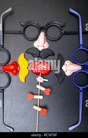 Moustache and a red mouth on wooden sticks on black background copy space for your text as the male and female concept, men and women - Stock Photo