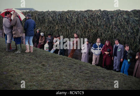 Grand National Horse race, Aintree, Liverpool, England UK. 1985 Spectators shelter from the rain in the lee of Bechers Brook fence. - Stock Photo