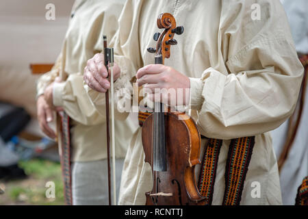 Riga. Latvia. A man in folk costume holds a violin in his hands. - Stock Photo