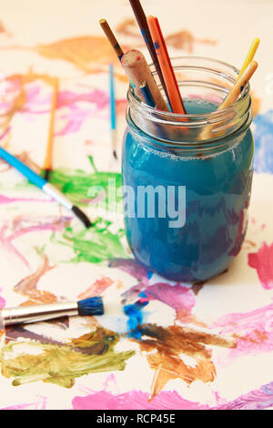 Kid's Messy paint brushes soaking in a glass jar of soapy water. - Stock Photo