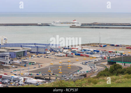 Lorries and cars waiting in lines to board a Cross Channel ferry at the Port of Dover. The cruise ship the Braemar is also seen in port. England, UK - Stock Photo