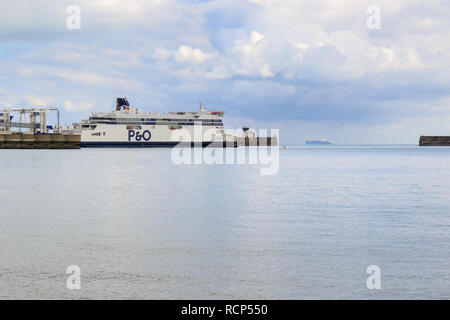 Side view of the P&O ferry Spirit Of France berthed at the port of Dover ferry terminal. Maersk line container ship on the horizon, Dover, England, UK - Stock Photo