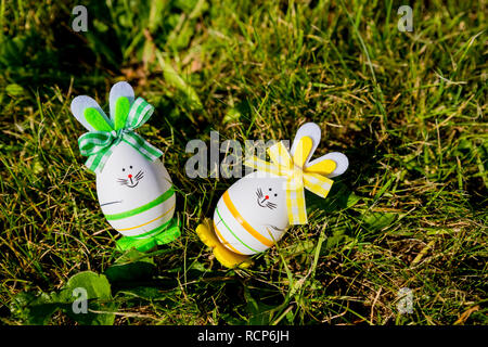 Cute creative photo with easter eggs as the Easter Bunny on green grass background. Happy easter greeting card.A Bunny Easter egg.Easter holiday concept with two cute handmade eggs: bunnies - Stock Photo