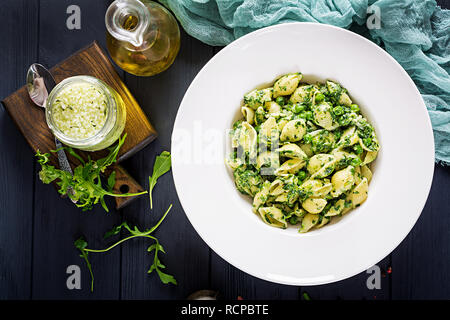 Conchiglie pasta with spinach and green pea pesto. Italian Cuisine. Vegan food. Top view - Stock Photo