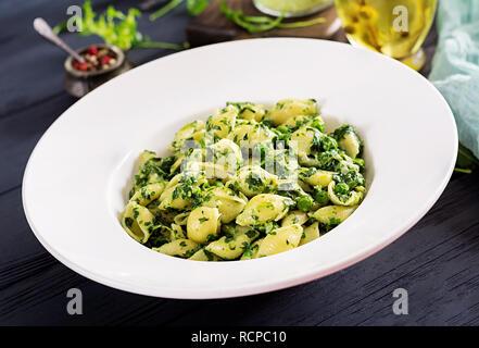 Conchiglie pasta with spinach and green pea pesto. Italian Cuisine. Vegan food. - Stock Photo
