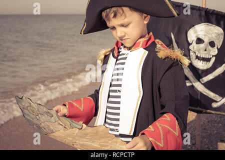 One happy little boy playing on the beach at the day time. He are dressed in pirate costume. Kid having fun outdoors. Concept of sailor on vacation. - Stock Photo
