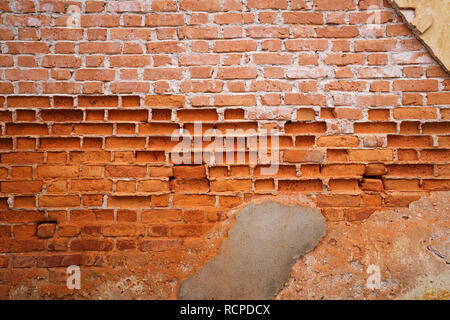 background image of old eroded plastered brick wall with most of the plaster and a lot of red brick missing - Stock Photo