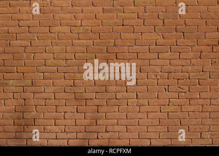 Antique weathered brick wall background abstract with deteriorating red clay bricks in traditional running bond pattern - Stock Photo