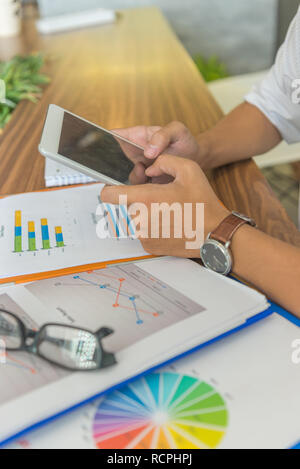 Male hands tapping on tablet screen while working - Stock Photo