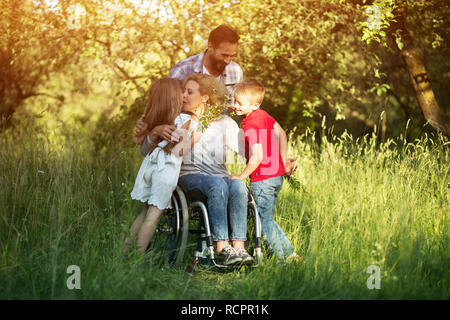 Woman in wheelchair kisses her son among family members - Stock Photo