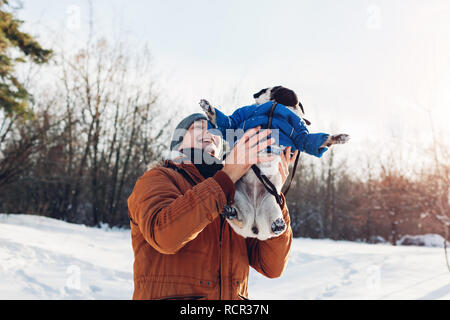 Pug dog walking with his master in winter forest. Man throwing his pet up for fun. Puppy wearing winter coat. - Stock Photo