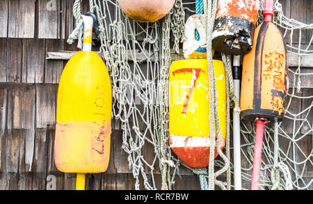 colorful lobster buoys with fishing nets hanging on a weathered shingle exterior wall in Massachusetts - Stock Photo