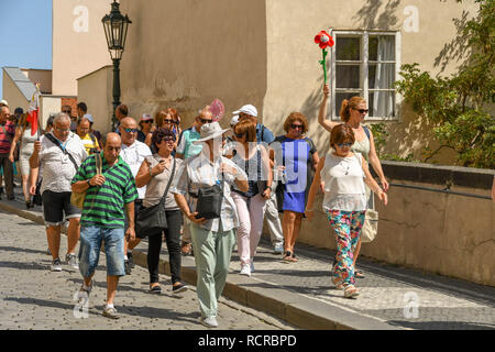 PRAGUE, CZECH REPUBLIC - JULY 2018: Group of tourists following a tour guide down a street near Prague Castle. The tour guide is holding up a brightly - Stock Photo