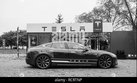 PARIS, FRANCE - NOV 29, 2014: New Tesla Model S showroom parked in front of the showroom with customers admiring the electric luxury car black and white - Stock Photo