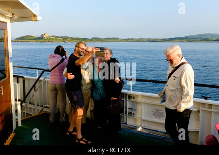 Family and friends take selfie photograph on board ferry between Oban and Craignure Mull - Stock Photo