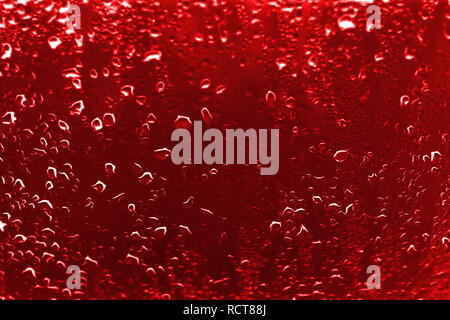 High contrast photo of drops of rain on a window glass with vivid red scarlet color - Stock Photo