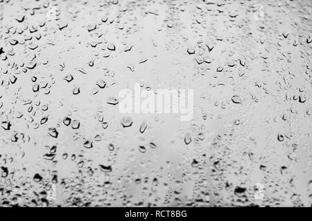 High contrast photo of drops of rain on a window glass with light pale gray color - Stock Photo