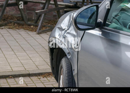 Damaged car - parked grey car with damaged panel on front near-side wing - Stock Photo