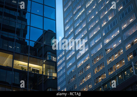 MONTREAL, CANADA - NOVEMBER 7, 2018: People working in open spaces offices in a skyscraper, seen from the outside, in the evening, in Montreal, Quebec - Stock Photo