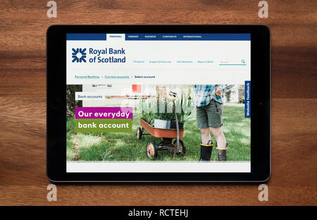 The website of Royal Bank of Scotland (RBS) is seen on an iPad tablet, which is resting on a wooden table (Editorial use only). - Stock Photo