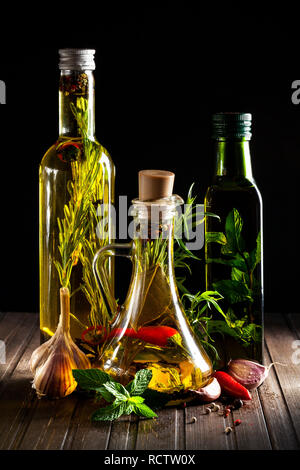 Bottles with oil, herbs and spices at wooden table on black background - Stock Photo