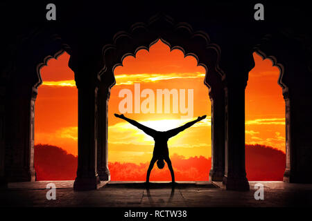 Man silhouette doing yoga advance handstand asana in old temple at orange sunset sky background - Stock Photo
