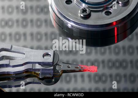 Computer hard drive, opened, read-write head on the disk, binary numbers reflected in the disc, symbolic image - Stock Photo