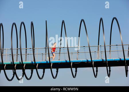 Jogger, runner, woman running on a pedestrian bridge, Slinky Springs to Fame, spiral-shaped bridge across the Rhine-Herne Canal - Stock Photo