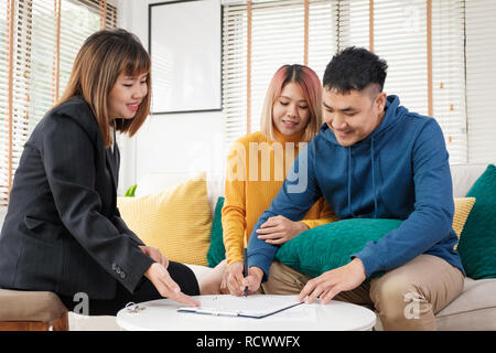 Asian couple sign home contract and handshake with realtor at living room in new home.buying new house real estate - Stock Photo