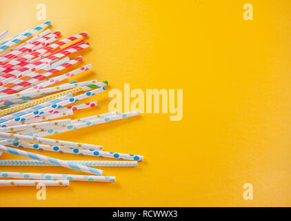 Drinking paper colorful straws for summer cocktails on yellow background. Top view. - Stock Photo
