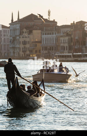 Venetian gondolier riding tourists on gondola at Grand Canal in Venice. - Stock Photo