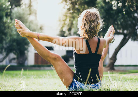 Woman in jeans black tank top doing upavistha konasana yoga pose in park. Female yogi in wide angle seated forward bend holding big toes with hands in nature - Stock Photo