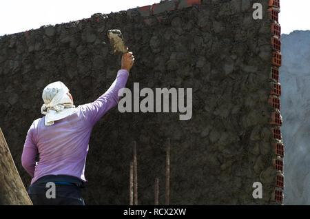 Construction worker - plastering and smoothing concrete wall with cement by a steel trowel - spatula aligns - Stock Photo