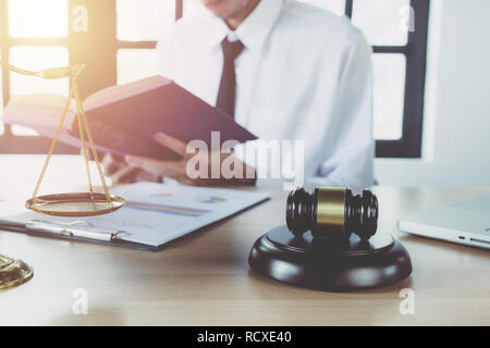 Male lawyer working with legal book on desk table with laptop,gavel,scale.justice and law concept. - Stock Photo