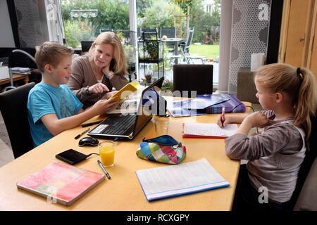 Siblings doing their homework in the living room, their mother is helping them