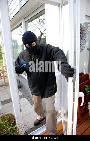 Burglar breaks open the door of the conservatory, symbolic image for domestic burglary - Stock Photo
