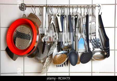 Various kitchen tools and utensils, hanging on a wall in a kitchen - Stock Photo