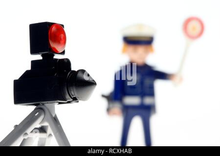 Playmobil figure, a policeman wearing a blue uniform, stop sign and a police radar device to measure the speed of vehicles - Stock Photo