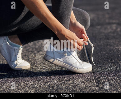 Running shoes - closeup of woman tying shoe laces. - Stock Photo