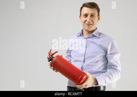 young man holding a fire extinguisher in his hands isolated on a light background - Stock Photo