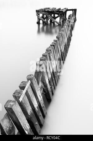 Theres many old remains of the wooden piers in the River Tyne and many of them have some lovely geometric forms. Using a long exposure to soften the w - Stock Photo
