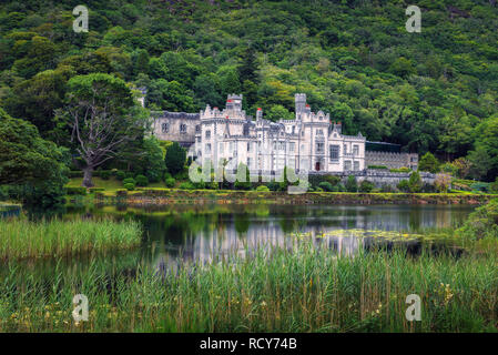 Kylemore Abbey in Ireland with reflections in the Pollacapall Lough - Stock Photo