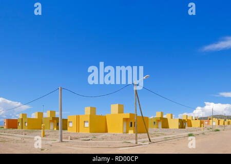 Yellow and orange colored row houses, terraced houses all built in the same style, Chilecito, La Rioja, Argentina - Stock Photo