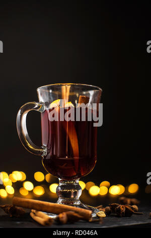 mulled wine with ingredients on the table and Christmas lights on background, cinnamon and orange in the glass - Stock Photo
