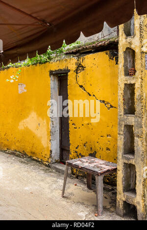 Stool beside bright yelllow old run down building next to doorway and under an awning in Hoi An, Vietnam - Stock Photo